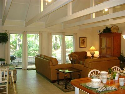 View From Kitchen of Large Open Living Room with Leather Furniture and Patio.