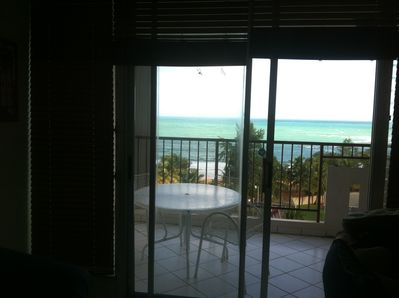 view of balcony and ocean from inside condo