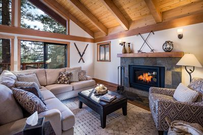 Great room has lofty beamed ceilings, gas fireplace, flat screen TV and deck