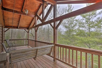 Sit on the 2-story deck at this vacation rental and enjoy the serene forest view