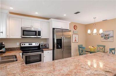 Fully equipped kitchen with brand new cabinetry and granite counters