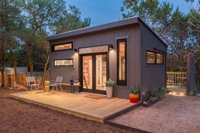 The front porch with seating, exterior lighting & the spacious, private grounds
