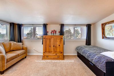 Master alcove with a twin trundle bed, sofa and TV