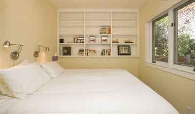 Quiet, cozy king-size bed with individual reading lamps and small library.