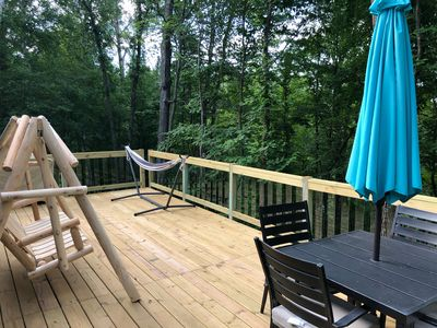 Large deck overlooking the lake with a table, hammock, log swing & gas grill