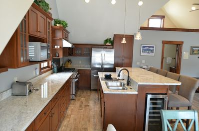Fully Equipped Kitchen  - The fully equipped kitchen has granite countertops and a bar for more seating.