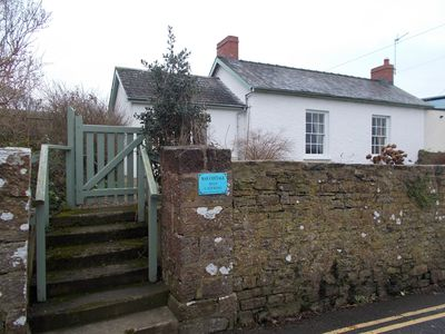 Cottage from the road, showing the wall and steps