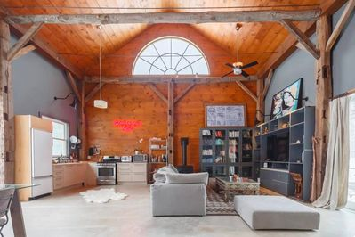 Open Floorplan. 1100 sq ft. Radiant Heated Polished Concrete Floors. RH Cloud Sofa. Samsung Smart TV. Kitchen, Dining Table. Reclaimed Wood Beams. 30 Ft Ceilings.
