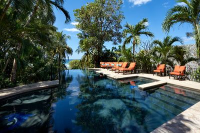 Large, private pool area surrounded by lush vegetation and plush seating.
