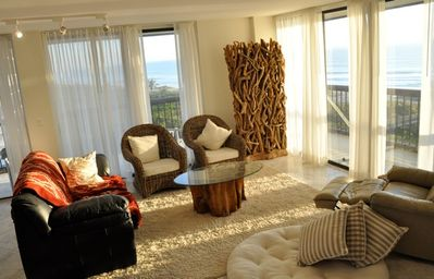 Living room with wrap around balcony overlooking the ocean