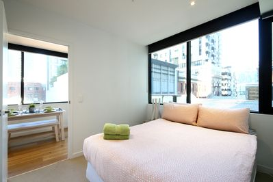 A bedroom with a queen sized bed & plush pillows.