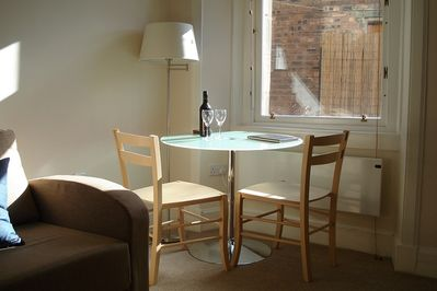 Dining area by the window. Table accommodates four, extra chairs are provided.