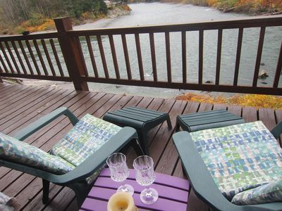 Large deck looking over the river, bbq, and table and chairs and firepit table