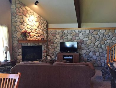A well furnished living area with a television and fireplace.