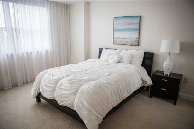 Plush queen size bed in the second bedroom with ocean and city views