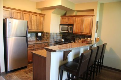 Fully equipped kitchen with counter seating for 4 and a heated slate floor.