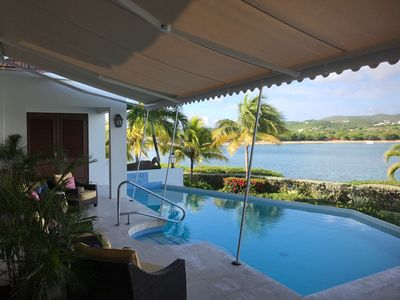 Pool deck covered by retractable awning.  Provides protection from rain and sun