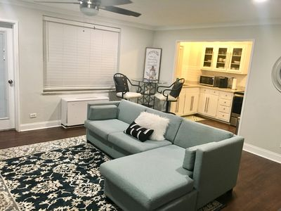 Dining area behind couch with deep seated bar height stools.