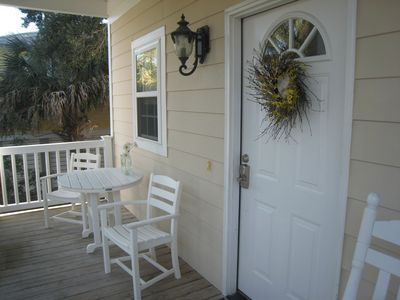 Welcoming front porch with table , chairs and rocking chairs for lazy days.