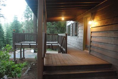 The covered front porch leads to large deck areas and the back yard