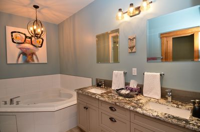 Double sinks and a corner heated Jacuzzi tub.
