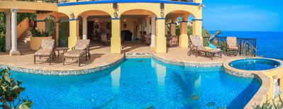 Comfy lounges and large pool with shaded ledge and waterfalls/grotto to the left