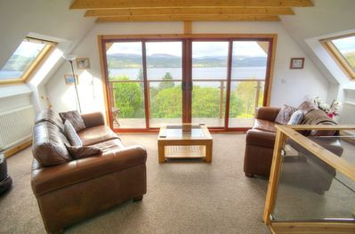 Upper living area, looking through patio doors and glass balcony to the loch