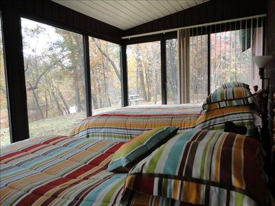 The sleeping porch has a queen and twin bed with a sleep sofa and dining table.