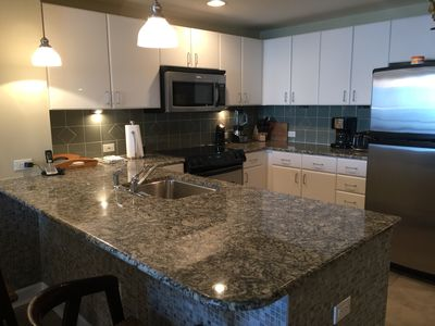 Kitchen with tile back splash and granite counter tops. Seating at bar as well!