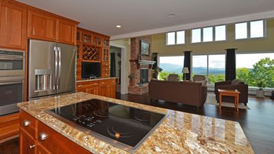 Gourmet kitchen looking into living room with amazing views from living room