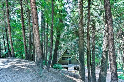 Towering trees surround this 1,100-square-foot A-frame cabin in the woods.
