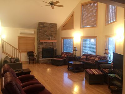 Main Living Room with wood burning fireplace. Open to kitchen and dining areas.