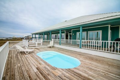 Pool deck and back deck leads down to waterfront with pier