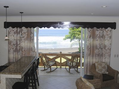 The living room and kitchen area open to a balcony that overlooks the beach.