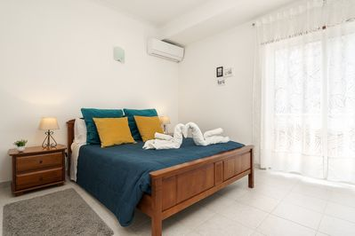 Bedroom with a double bed, spacious drawer closet & a bright and sunny balcony.