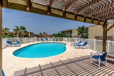 Pool Area - Find shade under the awning and plenty of sun on a poolside lounger at the shared pool.