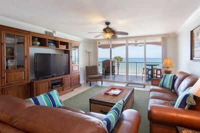 Living room w/ large flat screen TV and unobstructed beach views