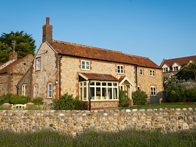 Photo for Gorgeous flint cottage overlooking the marshes, walking distance to beach
