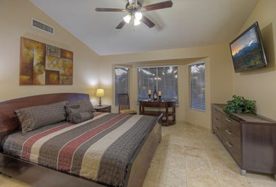 Elegant master suite with king bed, television and windows that brighten room with natural light