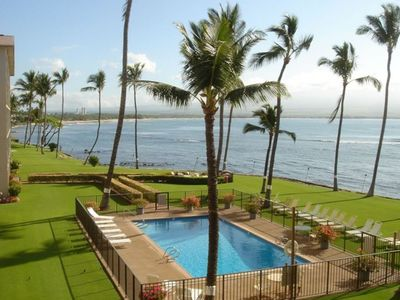 View from lanai. Overlook oceanfront palms in paradise swaying at sunrise.