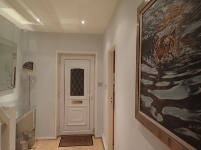Brightly lit hallway with large vanity mirror, coat hanger and artwork
