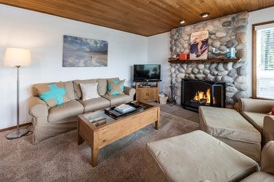 Wood-burning fireplace and comfy furnishings in the living room.