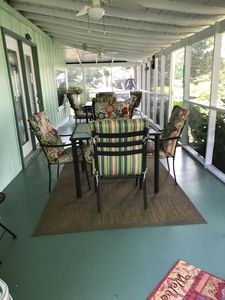 Screened in porch with ceiling fans, table seating for 8 plus rocking chairs.