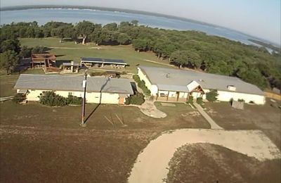 .Aerial view of the main house, bunk house, outdoor areas and the lake.