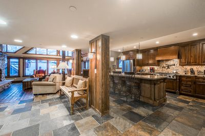 The main living floor is a sprawling open space with hardwood and stone tiles