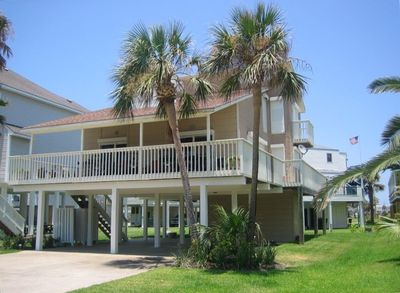 Beach House Front View of covered deck, palm trees and covered parking.