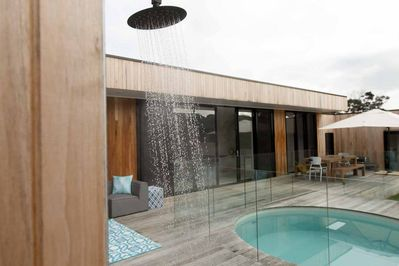 Deck area with outdoor shower, outdoor dining and heated plunge pool