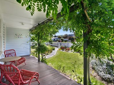 Sit and relax on the front verandah in the pretty cottage garden.