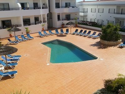 Communal pool with spacious poolside area, offering plenty of loungers