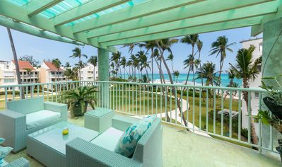 Shaded balcony with seating overlooking the blue Bavaro waters